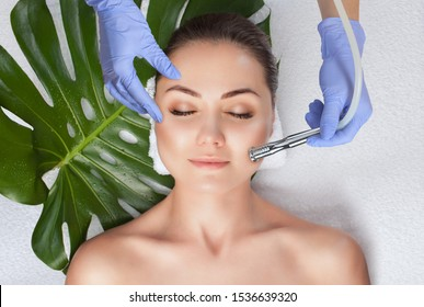 The cosmetologist makes the  Microdermabrasion procedure of the facial skin of a woman in a beauty salon.Cosmetology and professional skin care.