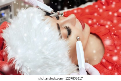 The cosmetologist makes the  procedure of Microcurrent therapy of a woman in Santa Claus hat on a background of snow. New Year's and Cosmetology concept.
