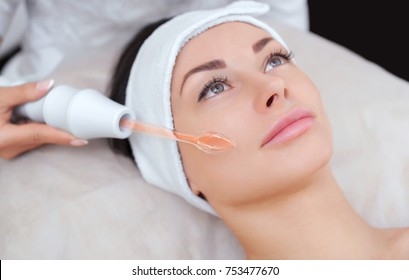 The cosmetologist makes the procedure Microcurrent therapy of the facial skin of a beautiful, young woman in a beauty salon.Cosmetology and professional skin care.