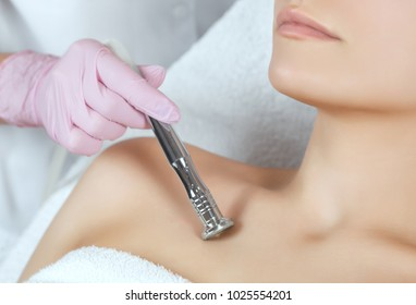 The cosmetologist makes the procedure Microdermabrasion of the decollete skin of a beautiful, young woman in a beauty salon.Cosmetology and professional skin care.