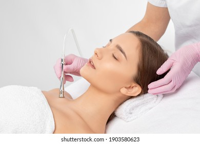 The cosmetologist makes the procedure Microdermabrasion of the face skin, neck and collarbone  of a beautiful girl in a beauty salon.Cosmetology and professional skin care.