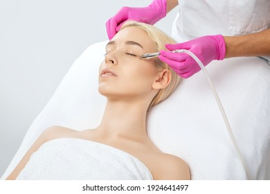 The cosmetologist makes the procedure Microdermabrasion of the face skin of a beautiful girl in a beauty salon.Cosmetology and professional skin care.