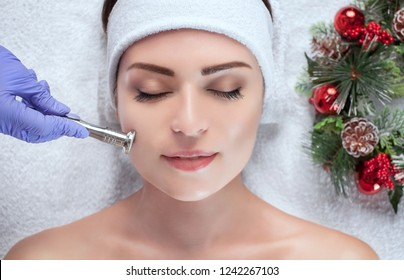 The cosmetologist makes the procedure Microdermabrasion of the facial skin of a beautiful, young woman in a beauty salon.Closeup woman face and new year wreath.