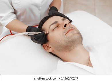 The cosmetologist makes the procedure Microdermabrasion of the facial skin of a man in a beauty salon.Cosmetology and professional skin care.