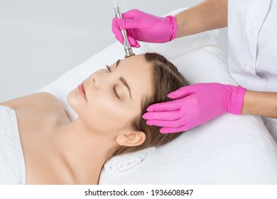 Cosmetologist makes  procedure microdermabrasion on the face against acne and blackheads near the eyes. Women's cosmetology in the beauty salon.