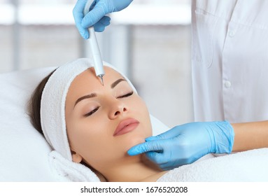 The cosmetologist makes the procedure treatment of Couperose and face cleaning of the skin of a beautiful, young woman in a beauty salon.Cosmetology and professional skin care.