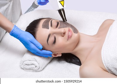 A cosmetologist is making carbon face peeling procedure in a beauty salon. Hardware cosmetology treatment.