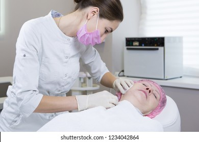 Cosmetologist making injection in face of senior woman. Skin aging, rejuvenation, face lifting procedures. Aged woman gets beauty facial injections in cosmetology clinic.