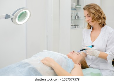 Cosmetologist making mesotherapy injection to woman patient. Microneedle mesotherapy. Female beautician at work. Hardware cosmetology. Dermapen, treatment of face zone, face rejuvenation.  Close up