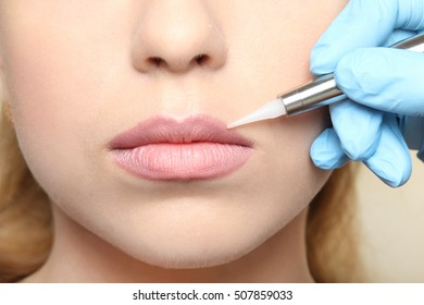 Cosmetologist  making permanent make up on lips, close up