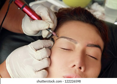 Cosmetologist making permanent makeup on face woman's .