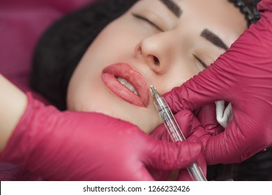 Cosmetologist making procedure. Dermatologist making an injection of hyaluronic acid. Close up still of lip injection. Lip booster procedure. Beauty salon service.