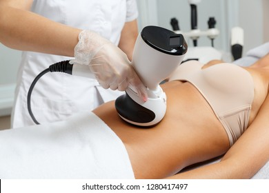 Cosmetologist making radio waves lifting therapy procedure for abdomen using latest technology for effective skin rejuvenation and tightening