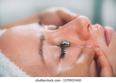 Cosmetologist massaging young woman's face with drainage sticks for dark circles