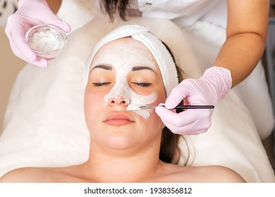 The cosmetologist in medical gloves holds a bowl with cosmetics, applying a brush mask on the client's face. Top view. Close up of face. Concept of professional cosmetology and treatment.