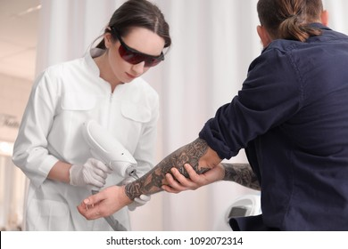 Cosmetologist with patient and professional tattoo removal laser in salon