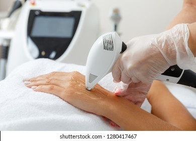 Cosmetologist  perfoms professional IPL cosmetology procedure on hands. Professional skin care treatment in a beauty salon