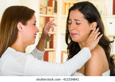 Cosmetologist performing facial hair removal using threading technique on brunette patient with painful face expressions