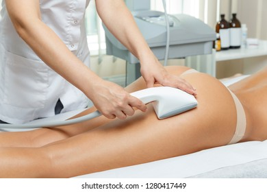 Cosmetologist performs vacuum roller massage   procedure for hips and but in cosmetological clinic using latest equipment for rejuvenation and treatment
