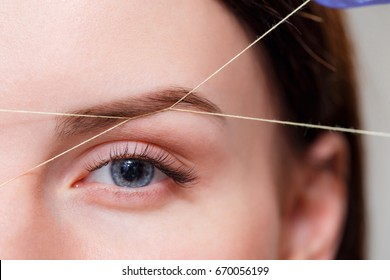 Cosmetologist plucks client eyebrows by thread
