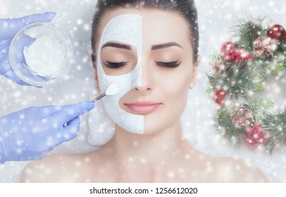 The cosmetologist for the procedure of cleansing and moisturizing the skin, applying a mask with stick to the face of a woman. Closeup woman face and new year wreath with snowflakes.