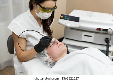 Cosmetologist in protective glasses conducts laser treatment of the skin for a young patient in a cosmetology clinic. Removal of vessels using a diode laser