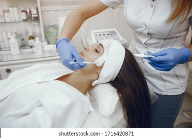 Cosmetologist treats client's skin. Woman with cosmetologist. Lady in a beauty studio.