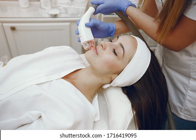 Cosmetologist use laser. Woman with cosmetologist. Lady in a beauty studio.