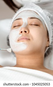 cosmetologist uses a face mask for a young woman