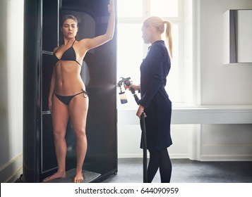 Cosmetologist using aerograph and spraying bodypaint tan to young pretty female hip in beauty salon.