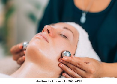 Cosmetologist using Chinese meditation balls for lymphatic drainage treatment of the face