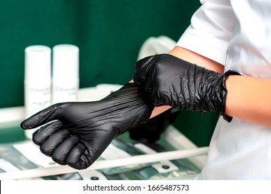 Cosmetologist wearing latex black gloves on her hands close up.