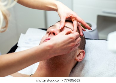 Cosmetologist woman is doing eyebrow modeling for man by Tweezers. Cosmetological clinic. Healthcare