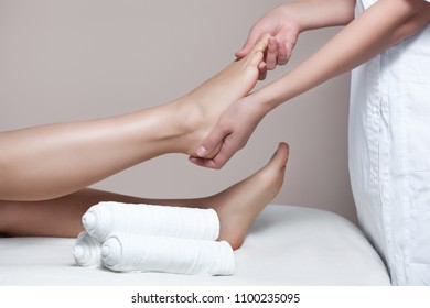 The cosmetologist wraps the leg  of the customer. Anti-cellulite procedure-STYX wrap.