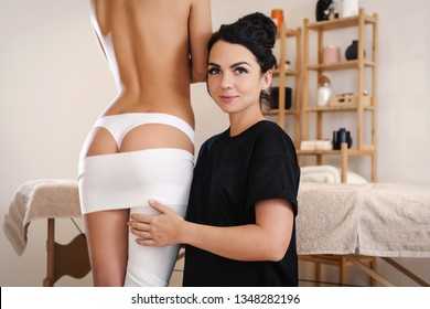 The cosmetologist wraps the leg of the customer. Anti-cellulite procedure of styx wrapping and banding. Young sexy slim woman in spa. Clear skin and perfect body concept