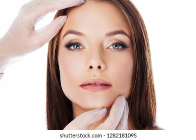 Cosmetology and aesthetic surgery. Portrait of a young attractive woman, clean skin and perfect proportions. Gloved hands touching face, isolated on white