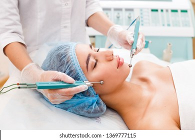 Cosmetology. Beautiful Woman At Spa Clinic Receiving Stimulating Electric Facial Treatment From Therapist. Closeup Of Young Female Face During Microcurrent Therapy.