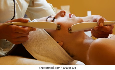 Cosmetology. Beautiful Woman At Spa Clinic Receiving Stimulating Electric Facial Treatment From Therapist. Closeup Of Young Female Face During Microcurrent Therapy. Beauty Treatment.
