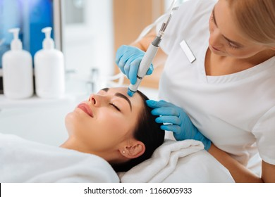 Cosmetology clinic. Professional female cosmetologist doing hydrafacial procedure while being a work
