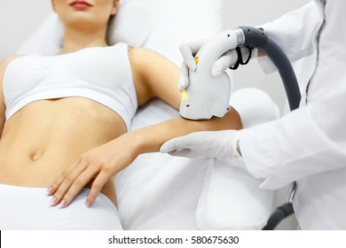 Cosmetology. Closeup Of Beautician Doing Laser Epilation Treatment On Beautiful Female Body, Removing Hair On Silky Skin. Woman Receiving Light Hair Removal Procedure In Beauty Salon. High Resolution