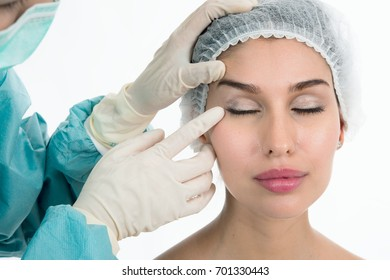 cosmetology, plastic surgery and beauty concept - beautiful young woman face and beautician hand in glove