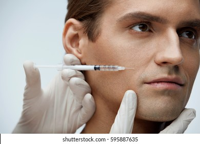 Cosmetology. Portrait Of Handsome Man With Perfect Skin Getting Beauty Treatment Indoors. Closeup Of Beautician Hands Injecting Filler Injection On Male Face. Skin Lift Procedure. High Resolution