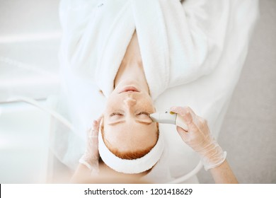 Cosmetology RF lifting equipment. Anti-age and anti-wrinkle apatherapy. Top view of beautiful woman in white bathrobe getting facial treatment at Cosmetology Salon.