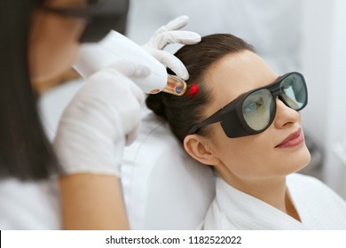 Cosmetology. Woman At Hair Growth Laser Stimulation Treatment