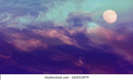 Cosmically beautiful, epic sky with clouds and moon, background. Violet, blue and pink clouds on bright, color, majestic and twilight Sky. Abstract background. Idyllic peaceful nature.