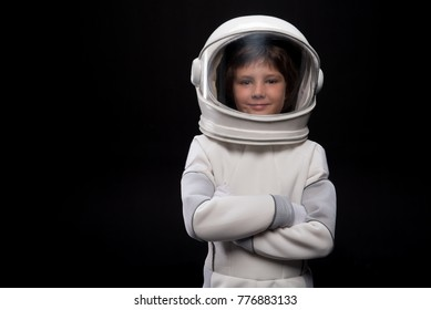Cosmonaut concept. Waist up portrait of positive little boy wearing white armor and helmet is standing with crossed arms while looking at camera with joy. Isolated background with copy space