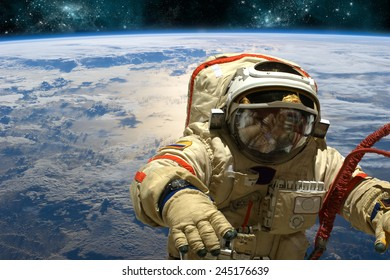 A cosmonaut floats in space above Earth. Stars shine in the background. Elements of this image furnished by NASA.