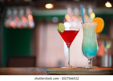 Cosmopolitan and Blue Hawaiian cocktails on the bar counter, blue and red drinks decorated with orange and lime in the pub