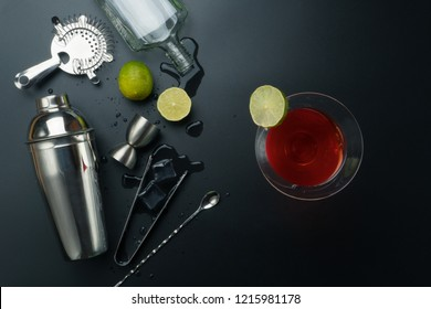 Cosmopolitan cocktail and bar equipments, stainless steel cocktail shaker and jigger, bar spoon with strainer, empty vodka bottle, the lemons and ice tongs with ice cubes on the table