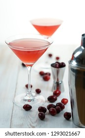 Cosmopolitan cocktail with cranberries, shaker and jigger. White wooden background, high resolution